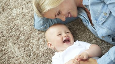 A breastfeeding mum plays happily with her baby, her sore nipples feeling better, thanks to using hydrogel pads