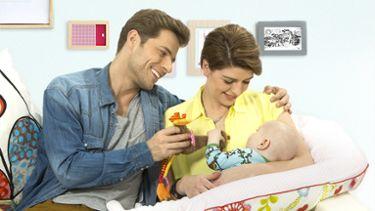 Mamma e papà che alimentano il bambino con il tiralatte Medela Mini Electric