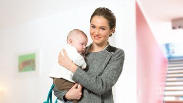 Mamma che tiene in braccio il bebè e tiralatte Swing di Medela